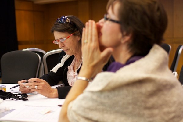 A selective focus photograph of two women sitting at a table - Corporate Event Photography