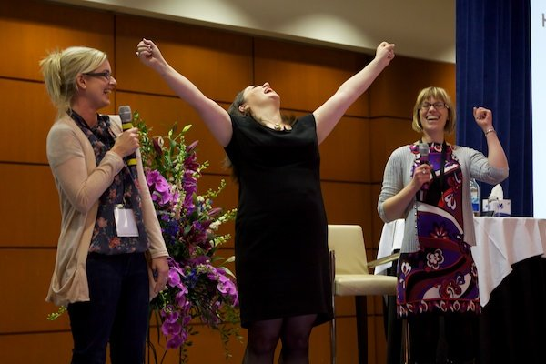 A woman showing joy in between two women on stage - Corporate Event Photography