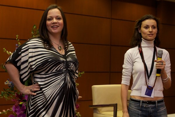 A speaker and woman stand at the front of a room - Corporate Event Photography