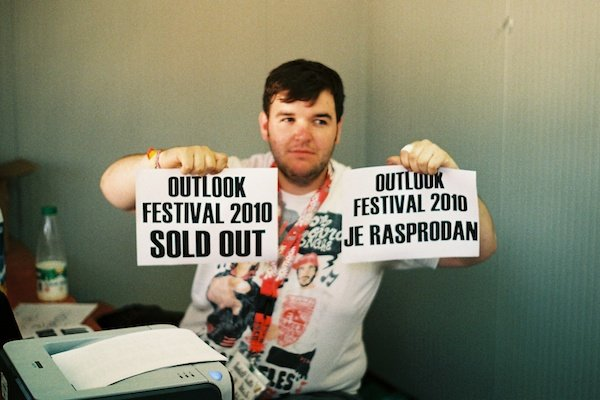 """Photo of a man holding two """"Festival sold out"""" signs taken on film"""