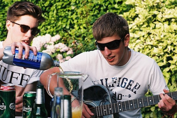 Photo of one guy pouring a drink and another one playing a guitar taken on film