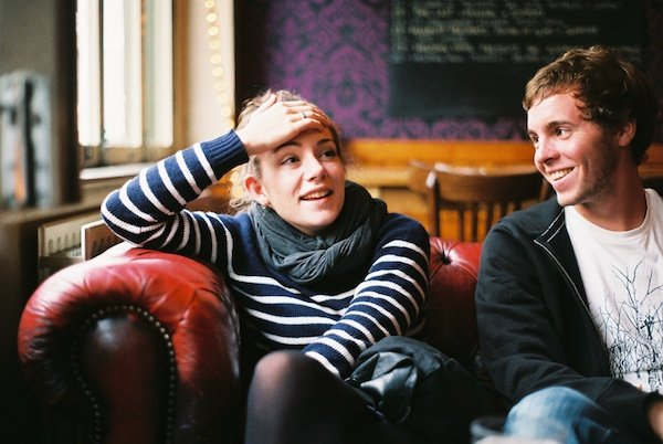 Photo of a woman and a man sitting on a couch taken on film