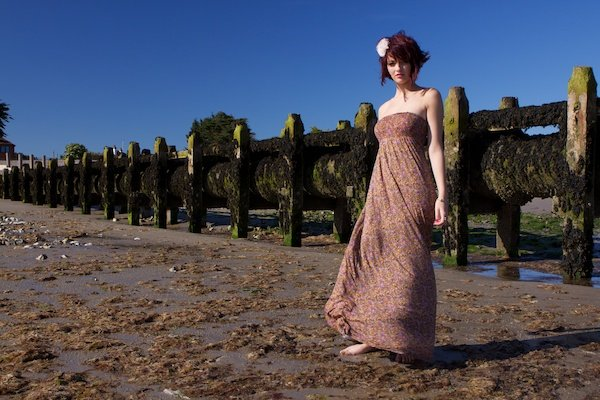 Portrait of a female model posing outdoors in front of a wooden structure, demonstrating the use of vertical lines in photography composition