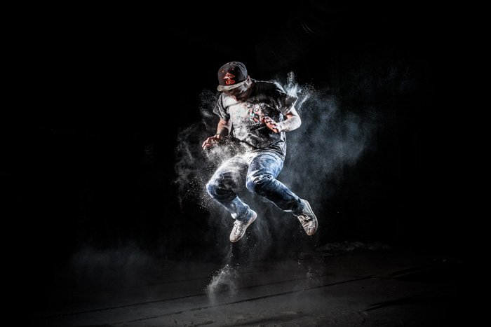 A man covered in white powder jumping in a dark setting with black background