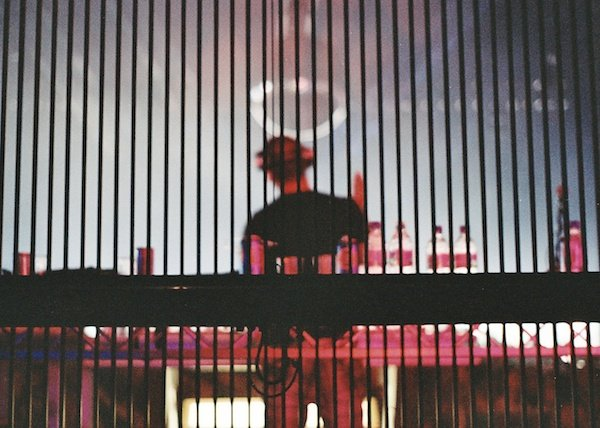 Blurred photo of a person on a stage taken from behind bars, demonstrating the use of vertical lines in photography composition