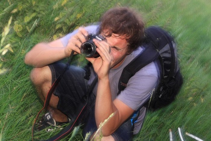 A blurry portrait of a photographer shooting with a DSLR outdoors