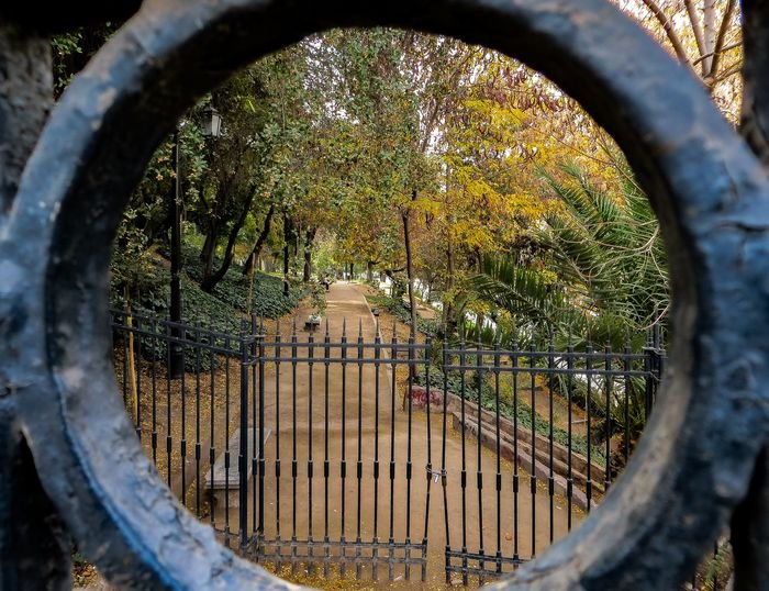 Photo of a park seen through a circular part of a gate in the foreground as a frame within a frame
