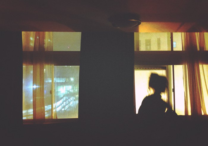 Dreamy portrait of a girl sitting on a windowsill