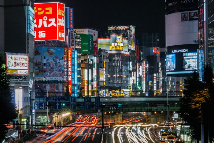 A busy Japanese cityscape with streaming light trails of cars whizzing by tall buildings