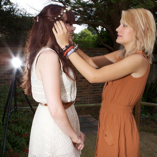 Photo of a young woman fixing another young woman's hair