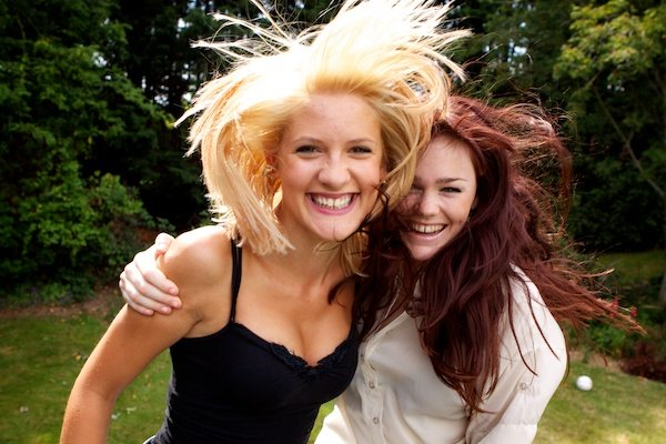 Photo of two young women in movement with their hair blown by the wind