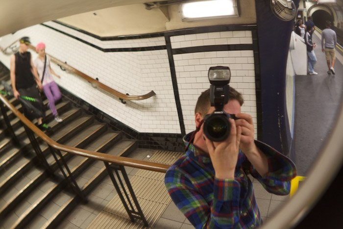A photographer taking a self portrait in a subway station mirror, demonstrating use of dynamic tension in photography composition