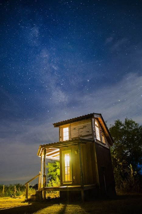 A wooden cabin taken at night in front of an impressive star filled sky