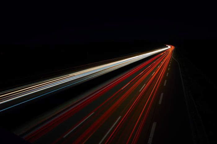 Streaming red and white light trails on a dark background shot at f/13 with a shutter speed of 25 seconds at ISO 100