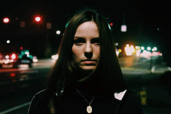 A night portrait of a female model on a street at night shot at a high ISO 3200, for 1/6 of a second at f/5
