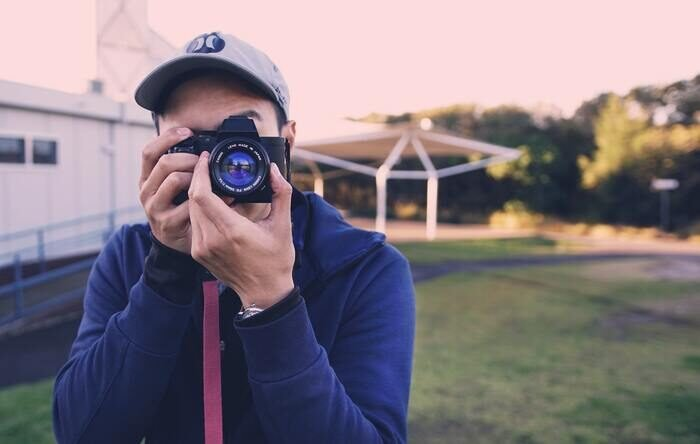 Photo of a guy holding a camera taking a photo