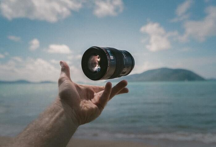 Photo of a hand throwing a lens in the air