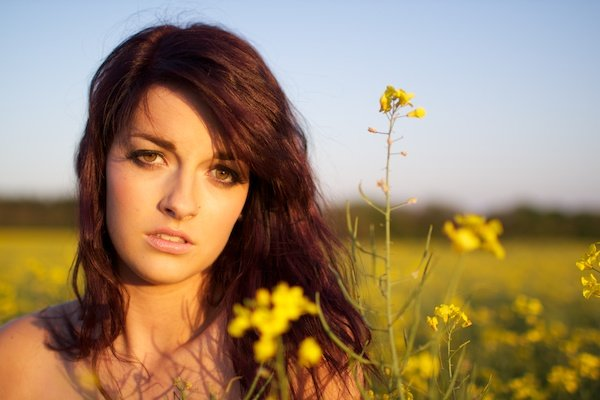 Portrait of a young woman in the field with flowers, demonstrating soft background technique in photography