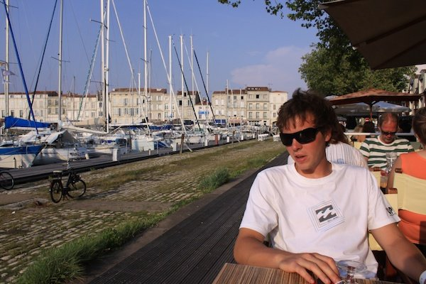 Casual shot of a male model posing in an outdoor cafe, showing the use of triangles in photography composition
