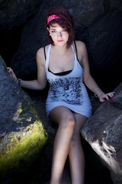 A portrait of a female model posing on rocks, showing the use of triangles in photography composition