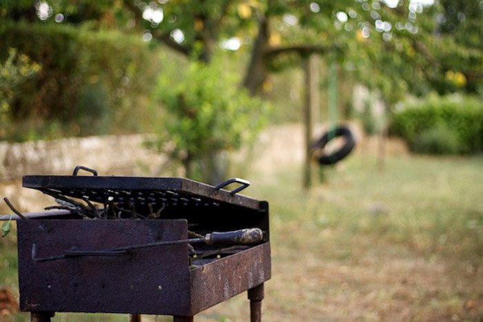 An old rusty barbecue and swing set shot with unbalanced composition