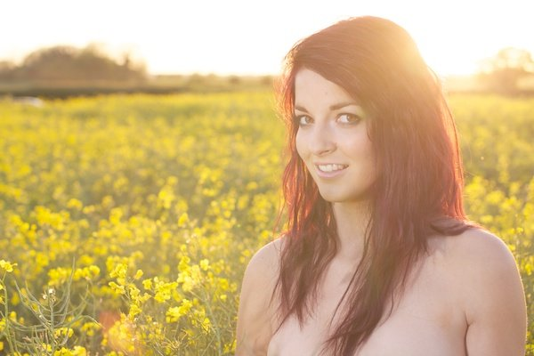 Photo of a young woman in the field of yellow flowers demonstrating editing with white brightness