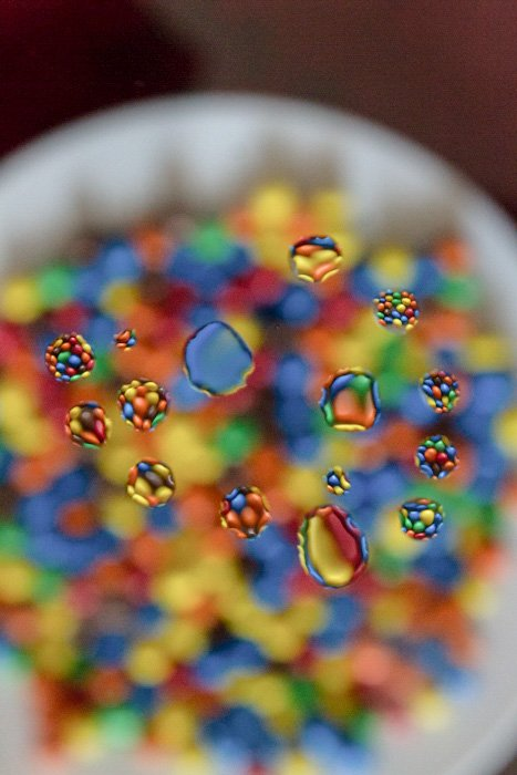 An image of water droplets with colorful m&m's behind -