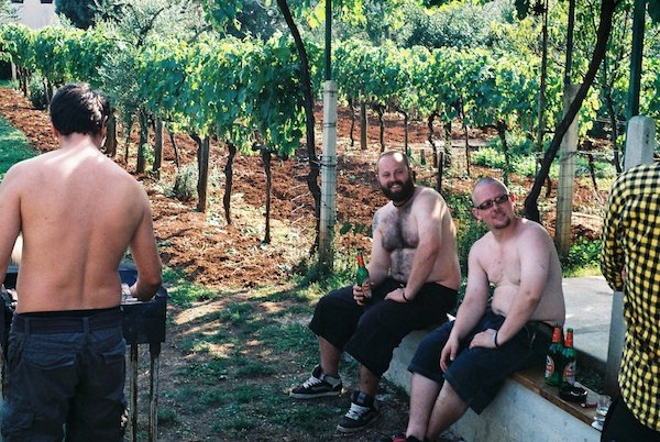 2 over-weight men drinking beer next to a grape vines with another man barbecuing next to them