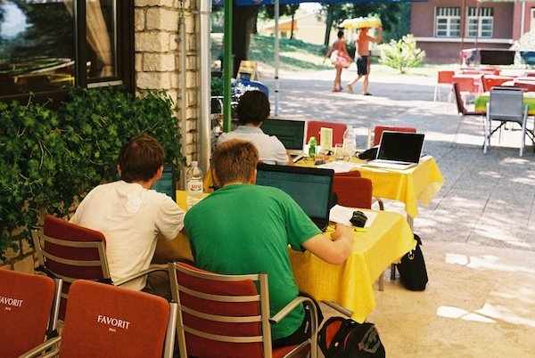 A scene on the terrace of a cafe with 3 young adults with their backs to us working on their laptops