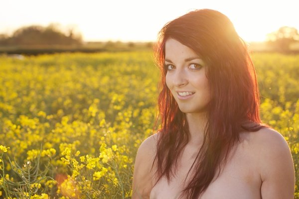 Photo of a young woman in the field of yellow flowers demonstrating editing with white recovery
