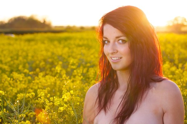 Photo of a young woman in the field of yellow flowers demonstrating editing with saturation