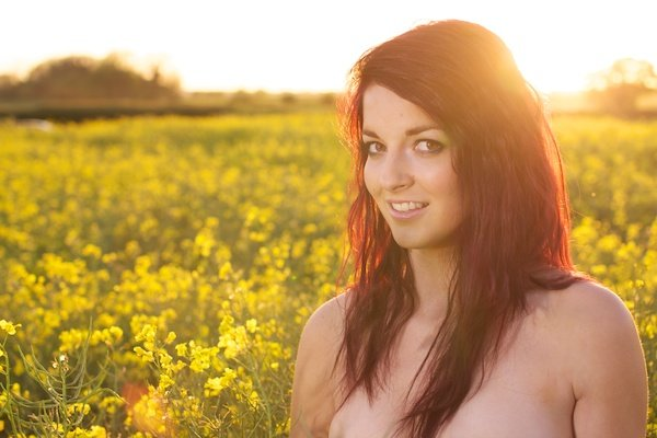 Photo of a young woman in the field of yellow flowers demonstrating editing with vibrancy