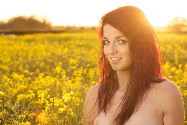 Photo of a young woman in the field of yellow flowers demonstrating editing with white balance