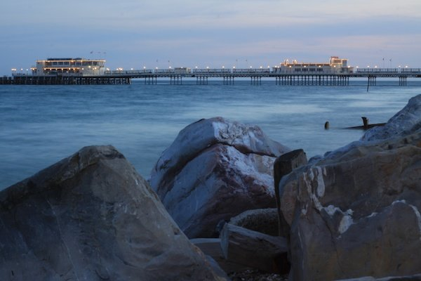 landscape photography of a pier with rocks in the foreground and boats in the background