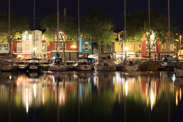 nighttime photography of boats in a harbor with water reflection of town lights