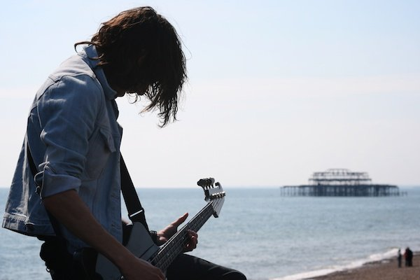 photo of male guitarist singing in outdoor setting with ocean background