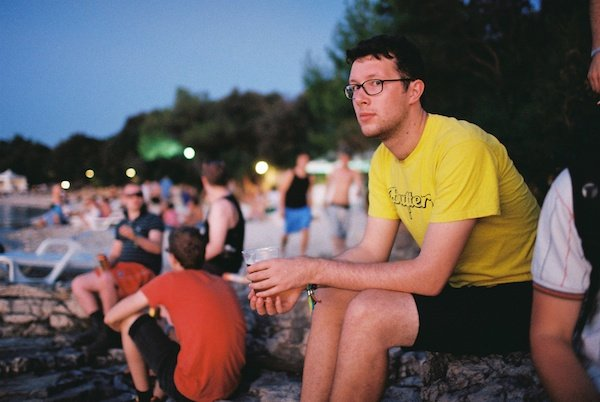 Photo of a young man in a yellow tshirt at some kind of a festival looking into teh camera