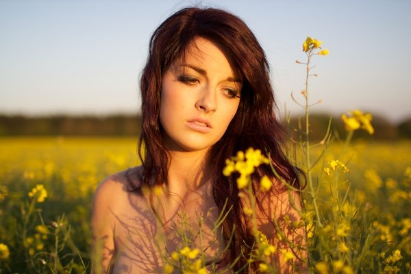 Photo of a young woman in the field of yellow flowers looking down