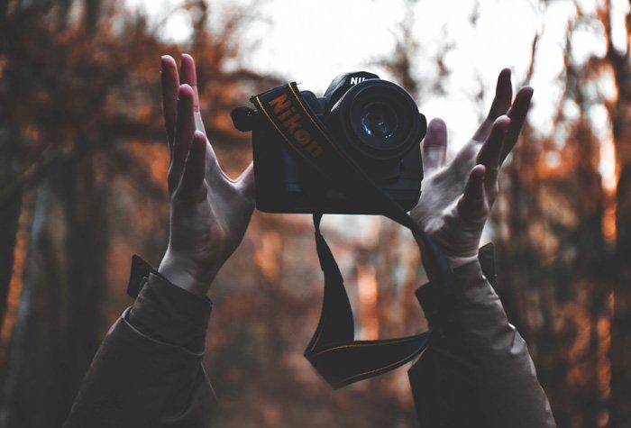 A photographer playfully throwing his Nikon DSLR camera into the air