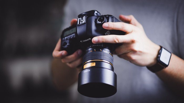 A photographer changing settings on a Canon EOS 5D