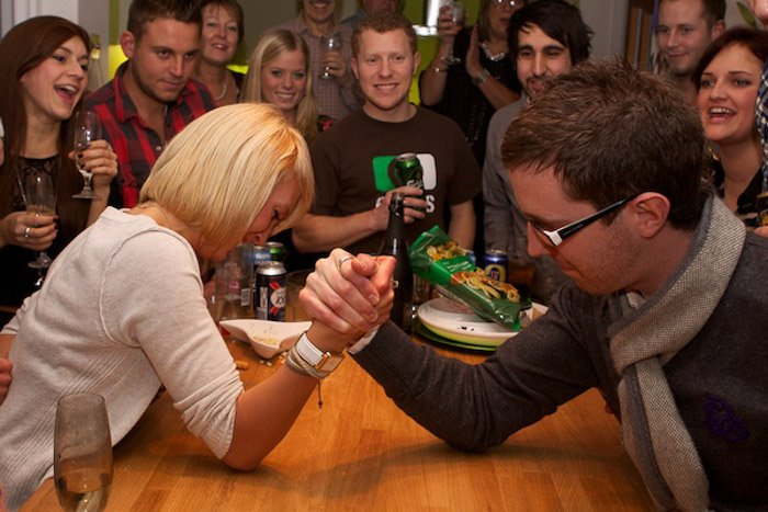 Funny portrait of two friends arm wrestling at a house party