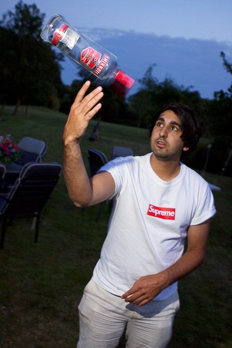 A man juggling a vodka bottle outdoors in low light - party photography