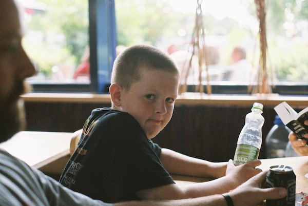 A boy holding a bottle looks at the camera - Window Light for Portraits