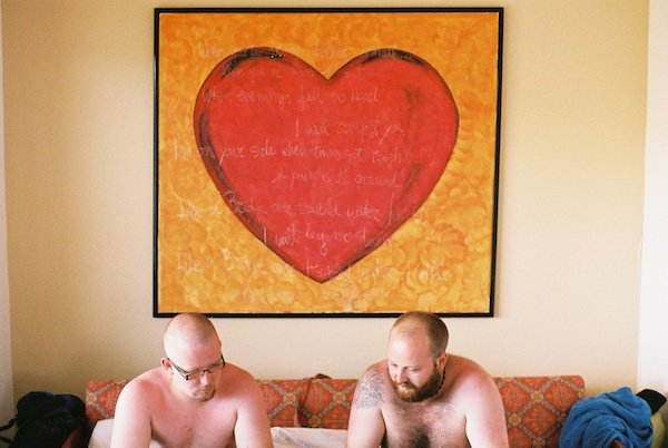Two men sit under a huge, red heart - Window Light for Portraits