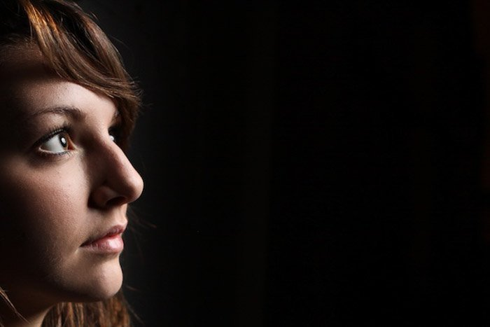 A portrait of a female model posing against a black background - interesting portraits