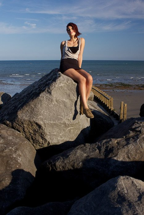 A portrait of a female model posing on rocks at the beach - interesting portraits