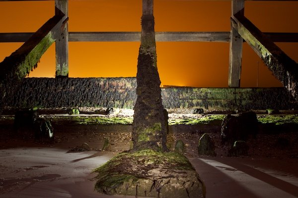 A stunning photo of an orange sky in the background of a wooden structure - light painting tips