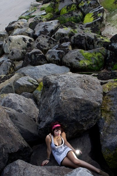 a girl sitting between huge rocks at the bottom of the frame