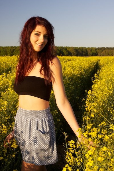 A woman in a skirt smiling in a field of flowers