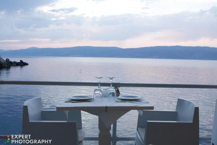 A table set by the sea at evening time with an 'Expert Photography' watermark on the bottom left corner